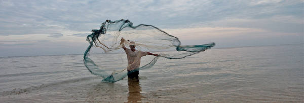 Fisherman throwing net